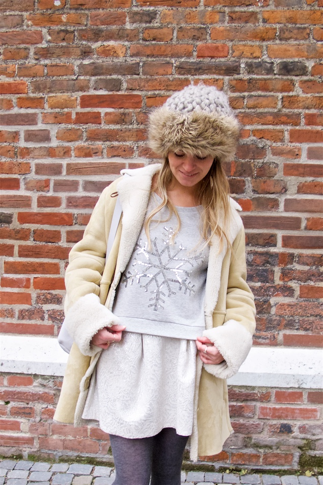 Russian Winter. Fashion and Style Blog Girl from Heartfelt Hunt. Girl with blonde loose curls wearing a sweater, brocade skirt, shearling jacket, faux fur beanie, backpack and Ugg boots.