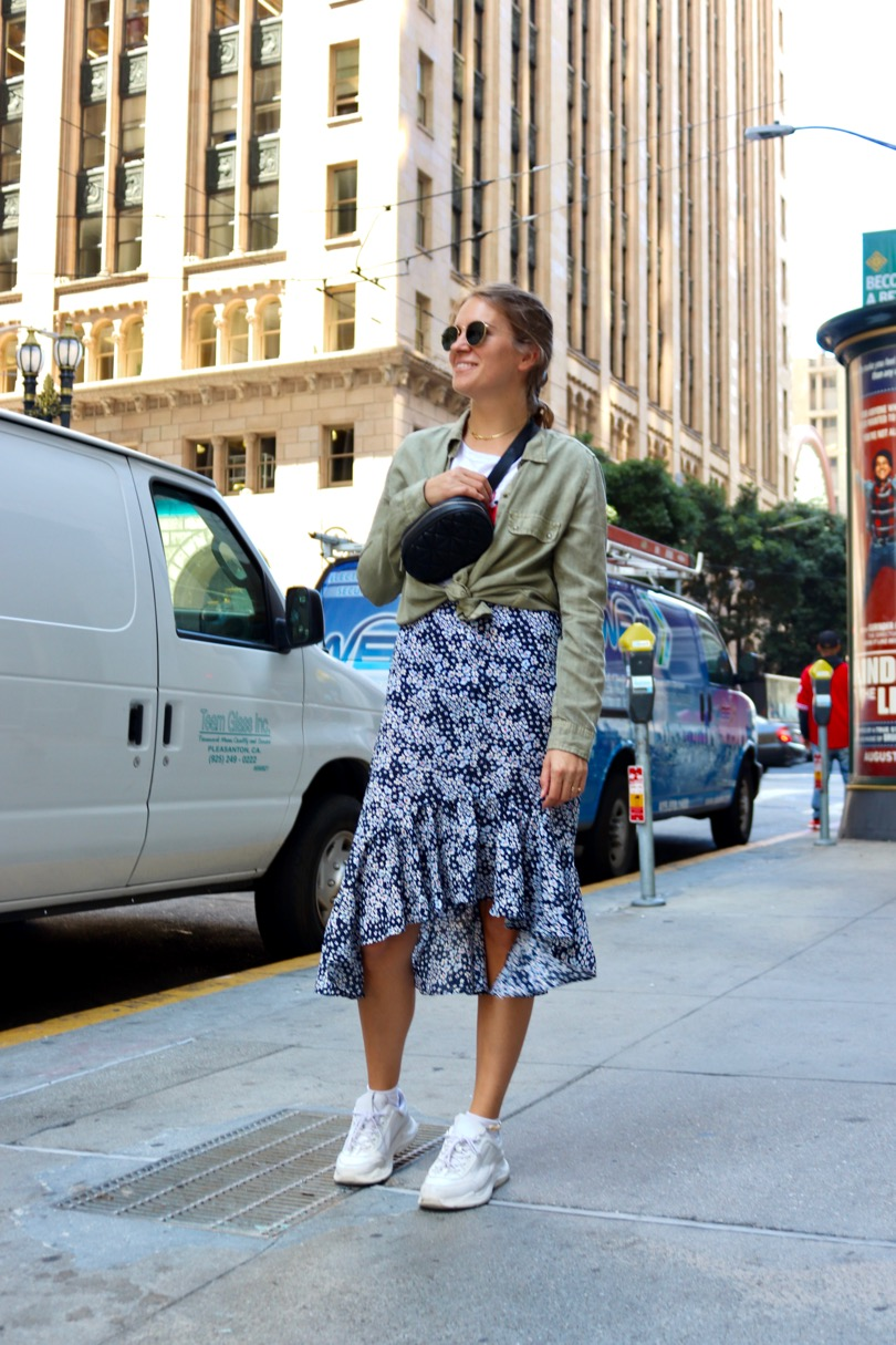 San Francisco. Fashion and Style Blog Girl from Heartfelt Hunt. Girl with blonde hair wearing a green shirt, white T-shirt, floral skirt, Ray-Ban sunglasses, belt bag and chunky sneakers.