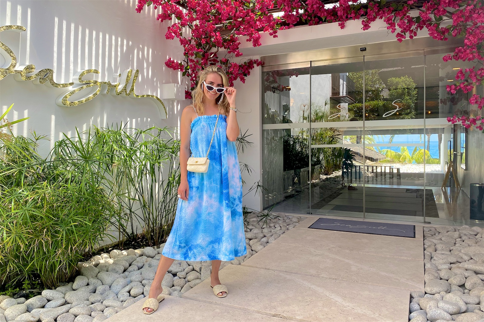 Sea Grill Marbella. Fashion Blogger Girl by Style Blog Heartfelt Hunt. Girl with blond hair wearing a DIY tie dye dress, sunglasses chain, white sunglasses, vintage Chanel bag and padded sandals.
