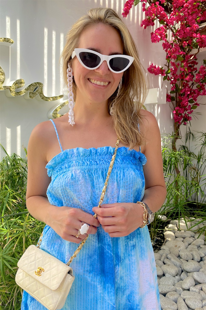 Sea Grill Marbella. Fashion and Style Blog Girl from Heartfelt Hunt. Girl with blonde hair wearing a DIY tie dye dress, sunglasses chain, white sunglasses, vintage Chanel bag and padded sandals.