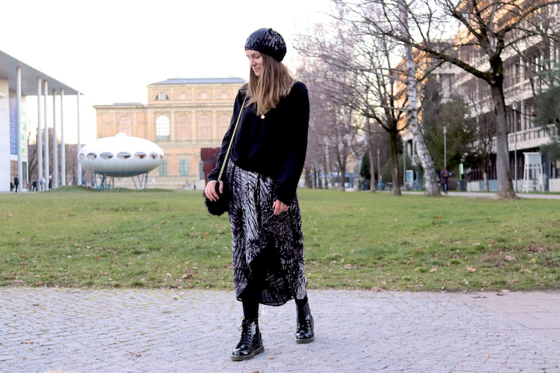 Sequined Beanie. Fashion Blogger Girl by Style Blog Heartfelt Hunt. Girl with blond hair wearing a sequined beanie, black turtleneck sweater, asymmetric midi skirt, faux fur bag and glossy boots.