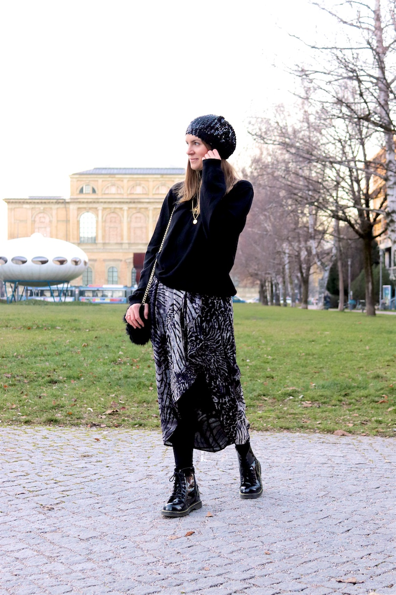 Sequined Beanie. Fashion and Style Blog Girl from Heartfelt Hunt. Girl with blonde hair wearing a sequined beanie, black turtleneck sweater, asymmetric midi skirt, faux fur bag and glossy boots.