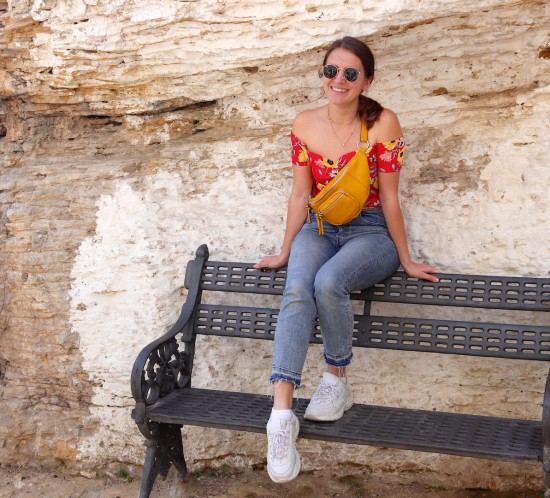 Setenil De Las Bodegas. Fashion Blogger Girl by Style Blog Heartfelt Hunt. Girl with blond, low ponytail wearing a floral off shoulder dress, mom jeans, Ray-Ban sunglasses, yellow belt bag and chunky sneakers.