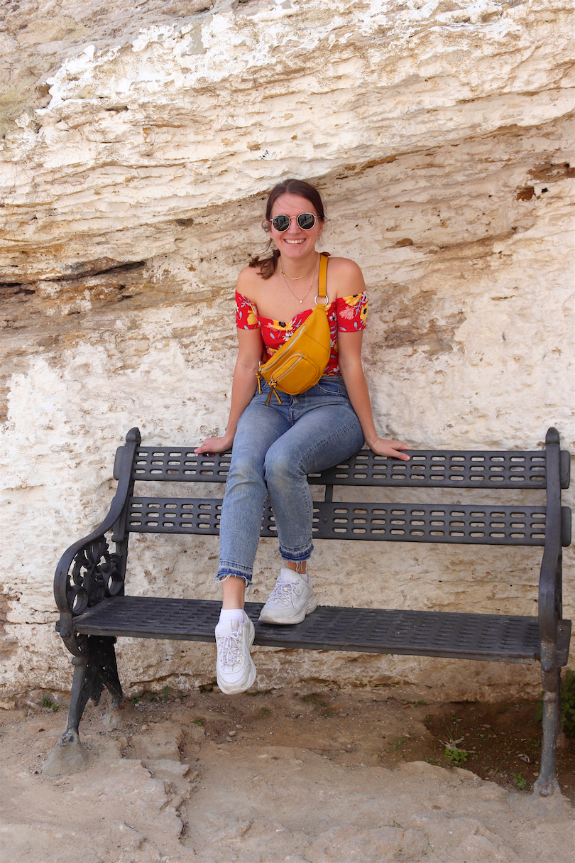 Setenil De Las Bodegas. Fashion and Style Blog Girl from Heartfelt Hunt. Girl with blonde, low ponytail wearing a floral off shoulder dress, mom jeans, Ray-Ban sunglasses, yellow belt bag and chunky sneakers.