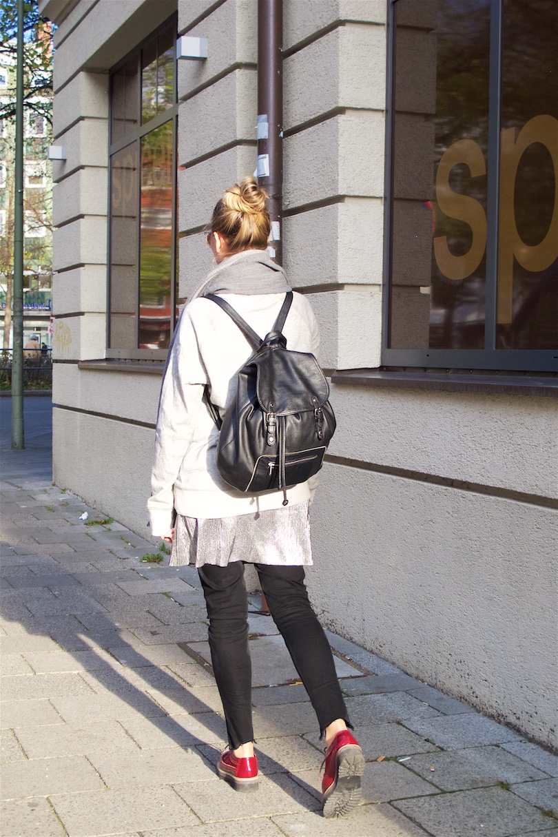 Silver Slip Dress. Fashion and Style Blog Girl from Heartfelt Hunt. Girl with blonde high messy bun wearing a silver slip dress, oversized sweater, jeans, backpack and burgundy brogues.