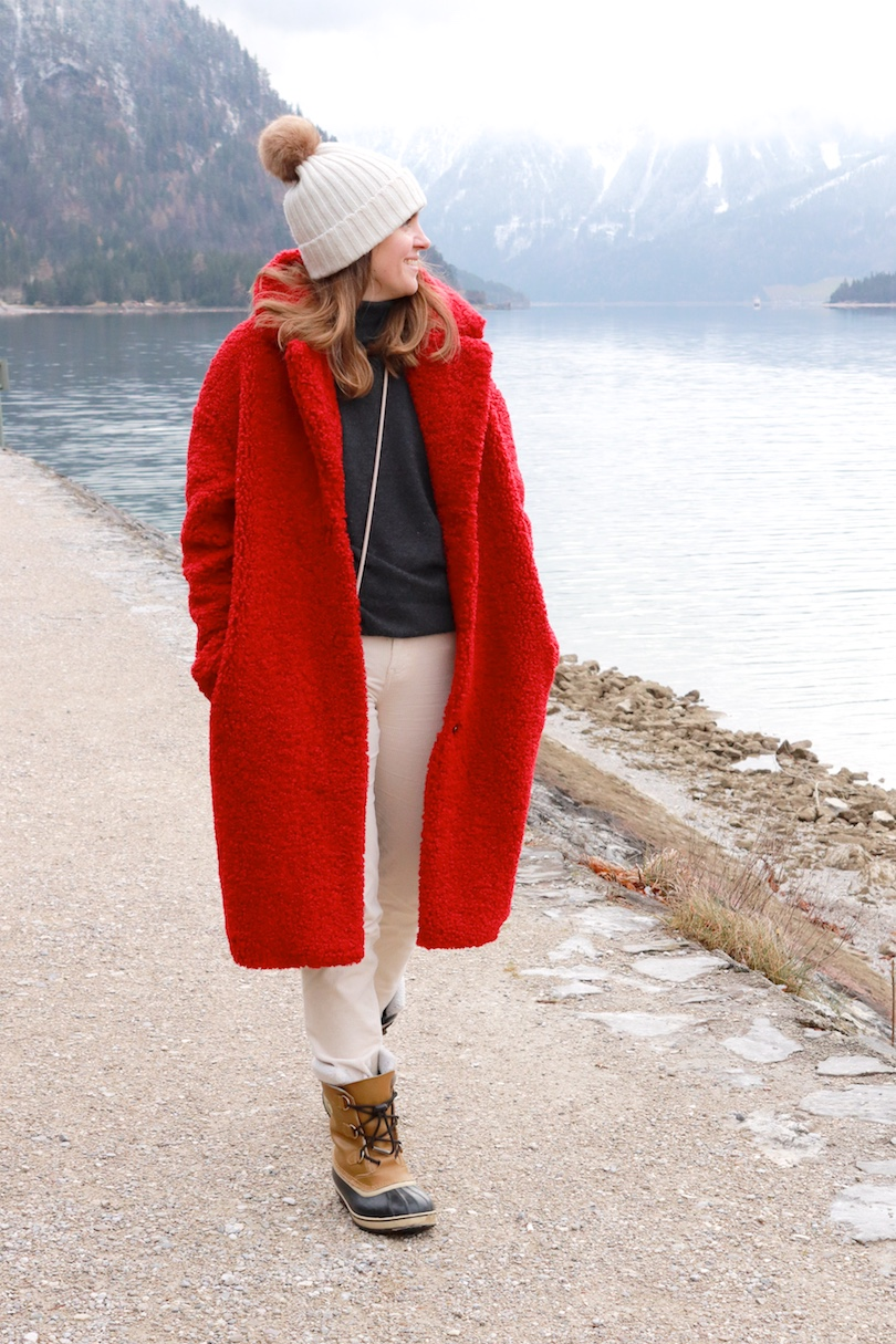 Sleigh Ride. Fashion Blogger Girl by Style Blog Heartfelt Hunt. Girl with blond hair wearing a red teddy coat, corduroy pants, turtleneck sweater, pompom beanie and Sorel boots.