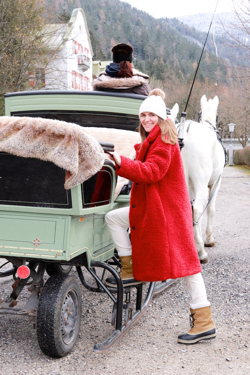 Sleigh Ride. Fashion and Style Blog Girl from Heartfelt Hunt. Girl with blonde hair wearing a red teddy coat, corduroy pants, turtleneck sweater, pompom beanie and Sorel boots.