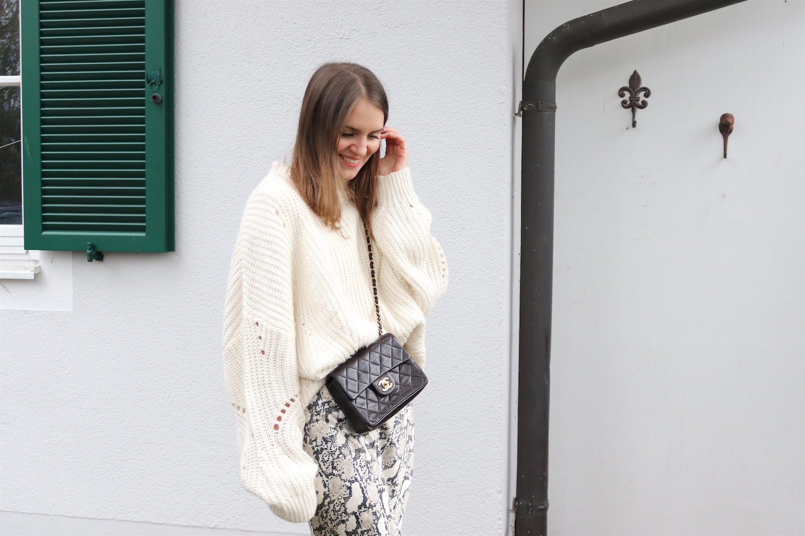 Snake Print Cozy Knit. Fashion Blogger Girl by Style Blog Heartfelt Hunt. Girl with blond hair wearing a snake print skirt, knit sweater, vintage Chanel bag and boots.
