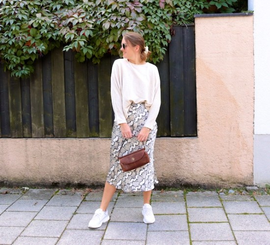 Snake Print Skirt. Fashion Blogger Girl by Style Blog Heartfelt Hunt. Girl with blond low bun wearing a snake print skirt, beige sweater, Ray-Ban sunglasses, scrunchie, baguette bag and chunky sneakers.