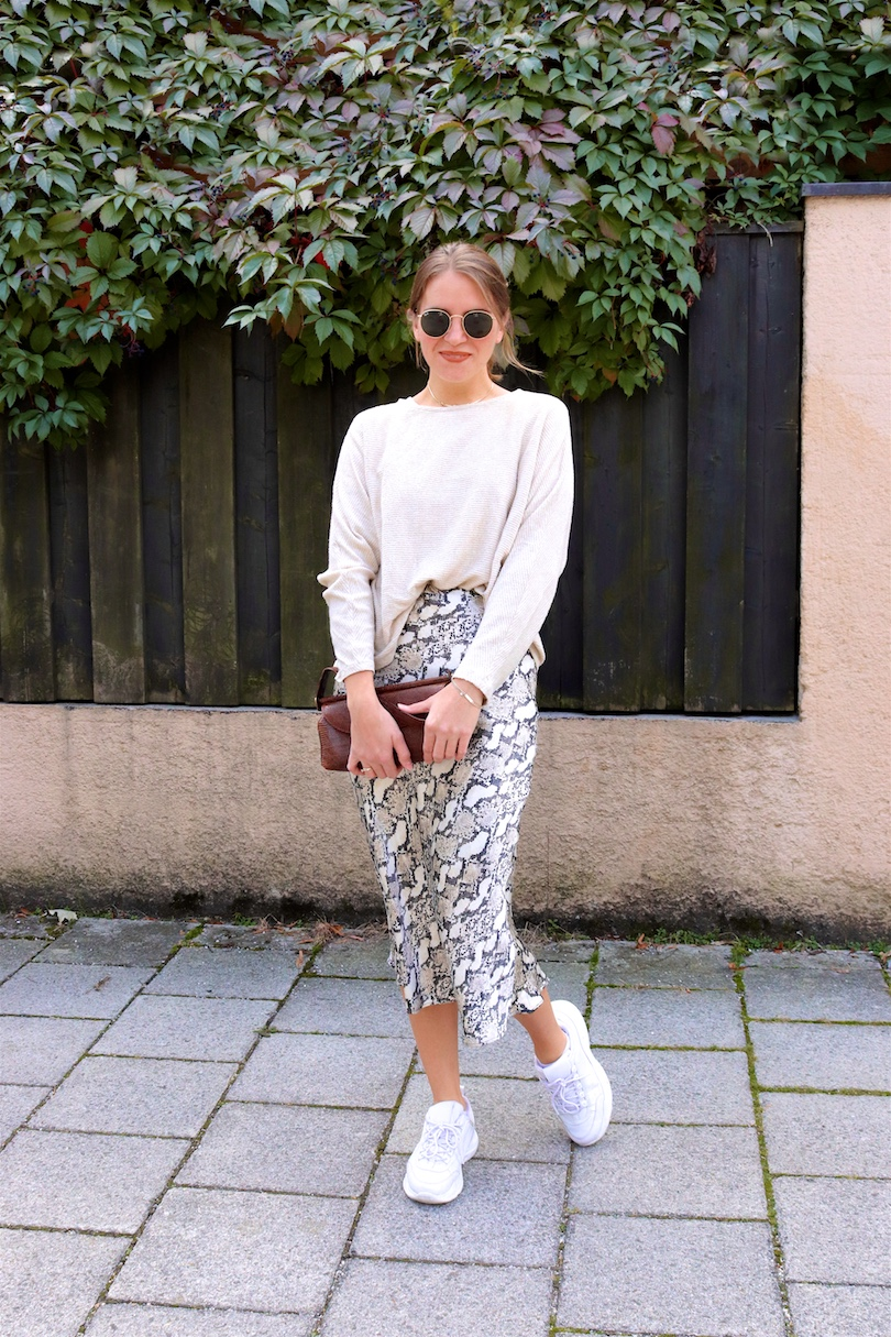 Snake Print Skirt. Fashion and Style Blog Girl from Heartfelt Hunt. Girl with blonde low bun wearing a snake print skirt, beige sweater, Ray-Ban sunglasses, scrunchie, baguette bag and chunky sneakers.