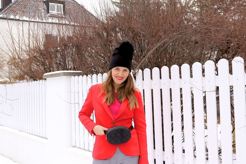 Snowy Valentines Look. Fashion Blogger Girl by Style Blog Heartfelt Hunt. Girl with blond hair wearing a red blazer, pink sweater, houndstooth check pants, beanie, belt bag and sock boots.