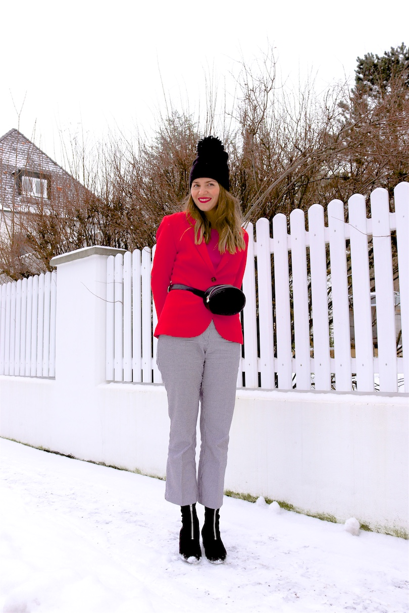 Snowy Valentines Look. Fashion and Style Blog Girl from Heartfelt Hunt. Girl with blonde hair wearing a red blazer, pink sweater, houndstooth check pants, beanie, belt bag and sock boots.