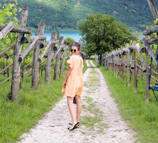 South Tyrol. Fashion Blogger Girl by Style Blog Heartfelt Hunt. Girl with blond high messy bun wearing a yellow gingham dress, Ray-Ban sunglasses, transparent bag with tortoiseshell handles and transparent flats.