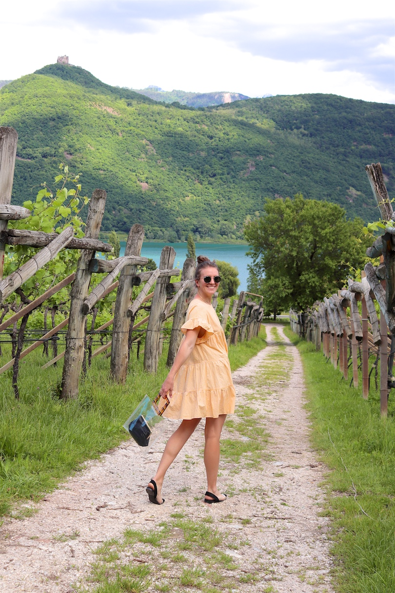 South Tyrol. Fashion and Style Blog Girl from Heartfelt Hunt. Girl with blonde high messy bun wearing a yellow gingham dress, Ray-Ban sunglasses, transparent bag with tortoiseshell handles and transparent flats.