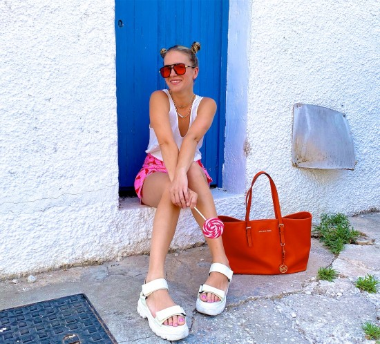 Space Buns. Fashion Blogger Girl by Style Blog Heartfelt Hunt. Girl with blond space buns wearing a floral skort, satin top, orange sunglasses, orange Michael Kors bag and chunky sandals.