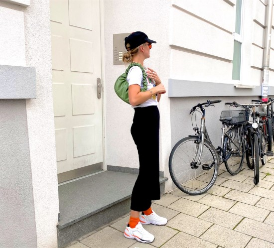 Sporty Weekend Look. Fashion Blogger Girl by Style Blog Heartfelt Hunt. Girl with blond, low bun wearing a SF Giants cap, orange sunglasses, graphic tee, black pants, green ruched bag, orange socks and sneakers.