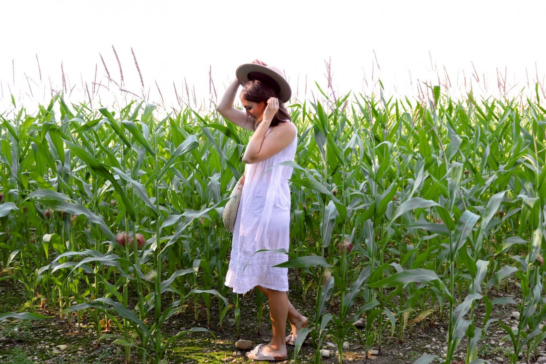 Summer Fields. Fashion Blogger Girl by Style Blog Heartfelt Hunt. Girl with blond hair with little braids wearing a white summer dress, panama hat, round straw bag and sandals.