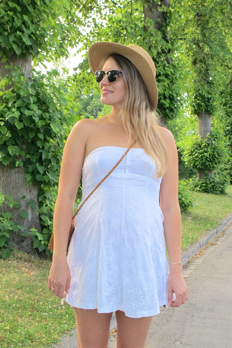 Summer White Straw. Fashion Blogger Girl by Style Blog Heartfelt Hunt. Girl with blond, long hair wearing a summer white dress, straw hat, Ray-Ban sunglasses, basket bag, denim shorts and espadrille sandals.