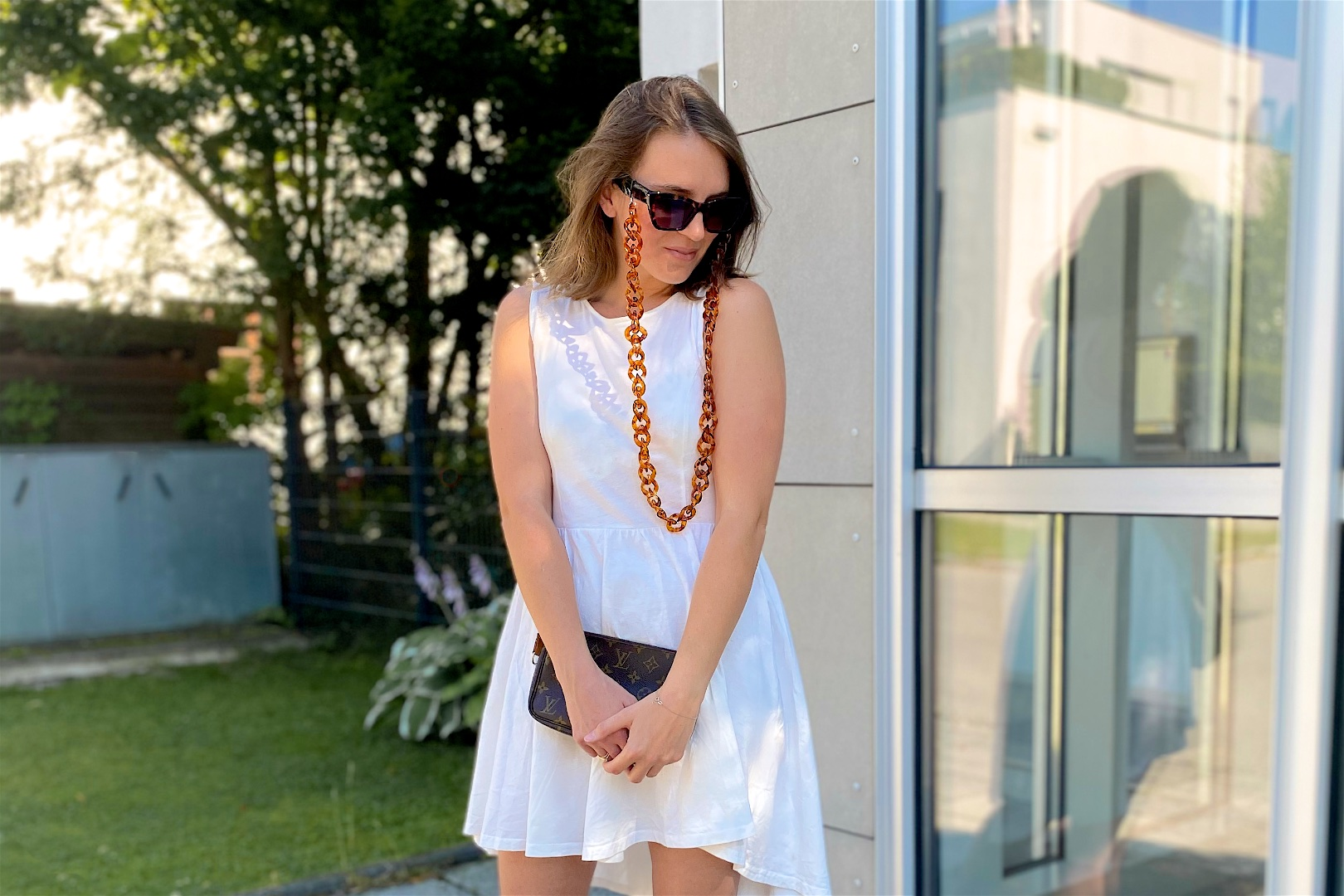 Sunglasses Chain. Fashion Blogger Girl by Style Blog Heartfelt Hunt. Girl with blond long bob wearing a sunglasses chain, sunglasses, asymmetric dress, Louis Vuitton pochette and sandals.