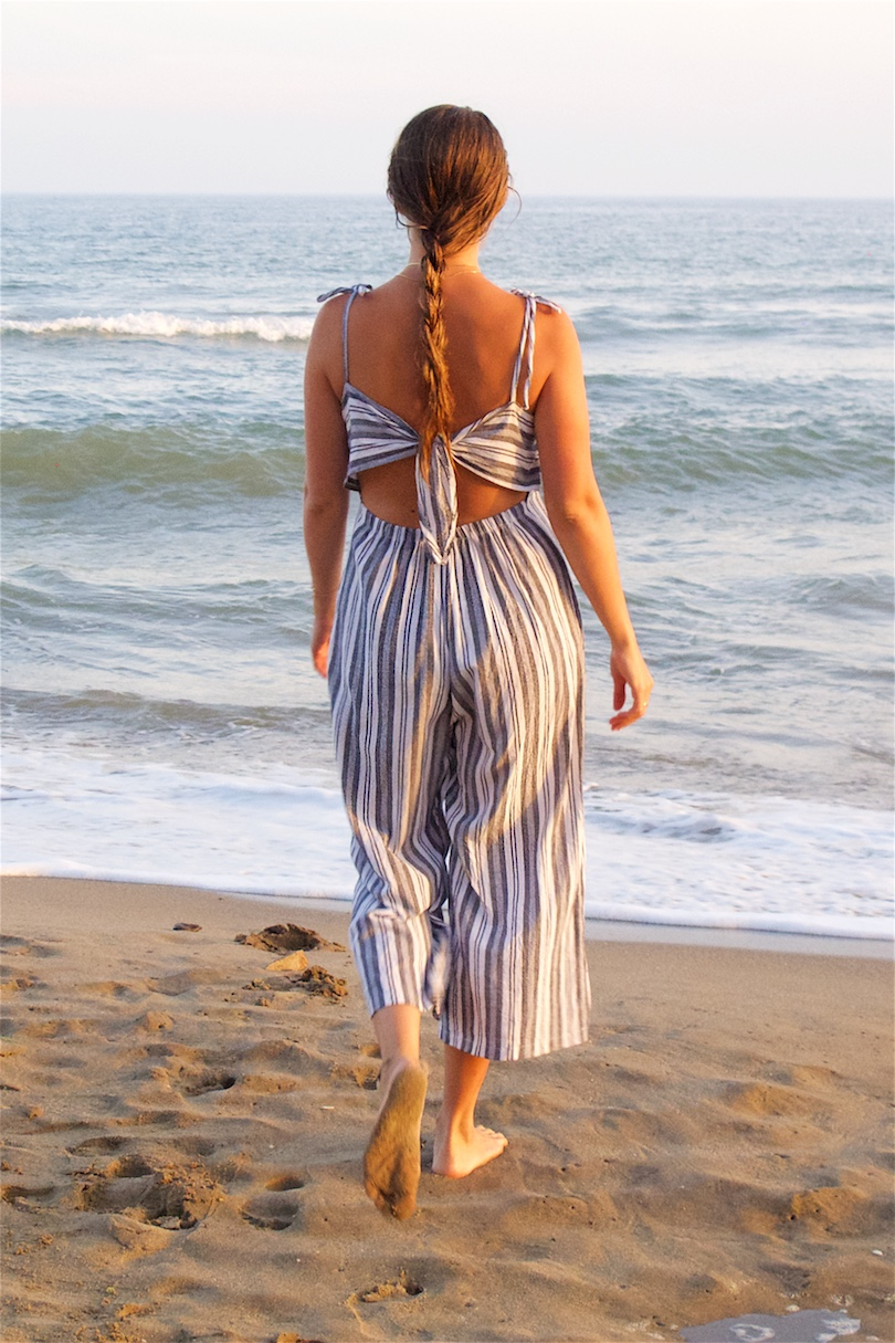 Sunset On The Beach. Fashion Blogger Girl by Style Blog Heartfelt Hunt. Girl with blond, long hair wearing a striped jumpsuit for a sunset on the beach.