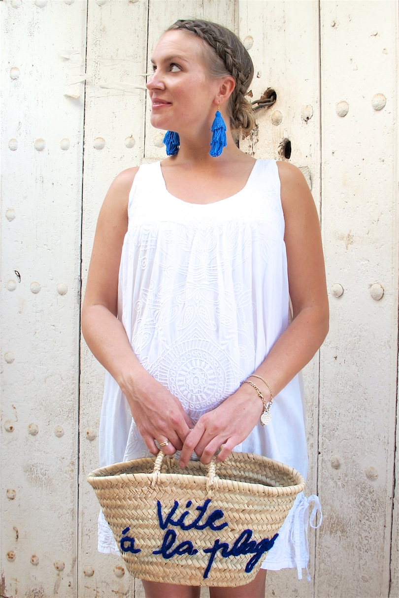 Tassel Earrings DIY. Fashion Blogger Girl by Style Blog Heartfelt Hunt. Girl with blond dutch braided low bun wearing tassel earrings, white summer dress, Ray-Ban sunglasses, basket bag and espadrille sandals.