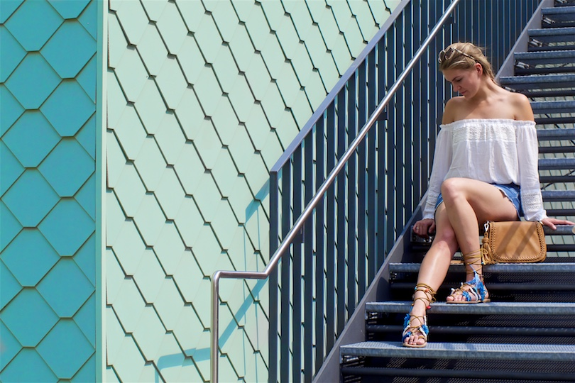 Tassel Sandals. Fashion and Style Blog Girl from Heartfelt Hunt. Girl with blonde dutch braid wearing a white off-shoulder top, denim shorts, tassel bag, tassel sandals and sunglasses.