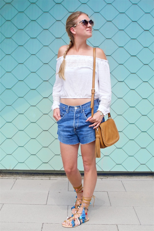 Tassel Sandals. Fashion Blogger Girl by Style Blog Heartfelt Hunt. Girl with blond dutch braid wearing a white off-shoulder top, denim shorts, tassel bag, tassel sandals and sunglasses.