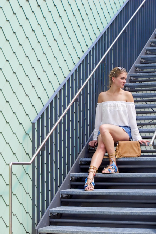 Tassel Sandals. Fashion and Style Blog Girl from Heartfelt Hunt. Girl with blonde dutch braid wearing a white off-shoulder top, denim shorts, tassel bag, tassel sandals and sunglasses.