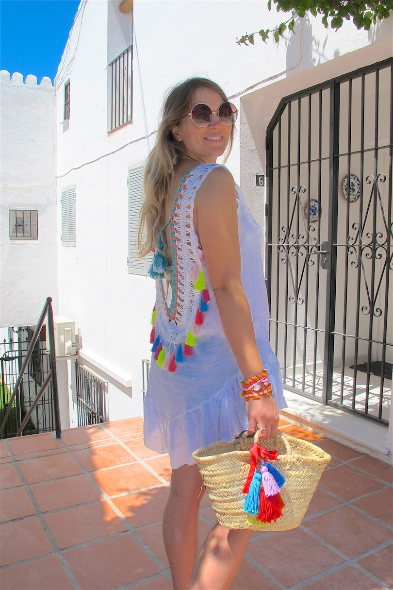 Tassels and Bougainvilleas. Fashion and Style Blog Girl from Heartfelt Hunt. Girl with blonde, long hair wearing a backless tassel top, basket bag with tassels, round sunglasses, denim shorts and sandals.