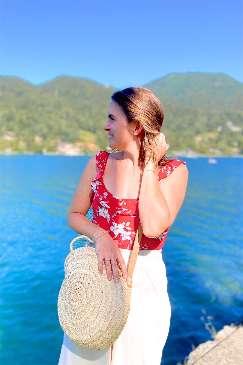 Tegernsee Boating. Fashion and Style Blog Girl from Heartfelt Hunt. Girl with blonde long bob wearing a red floral bodysuit, beige loose pants and round straw bag.