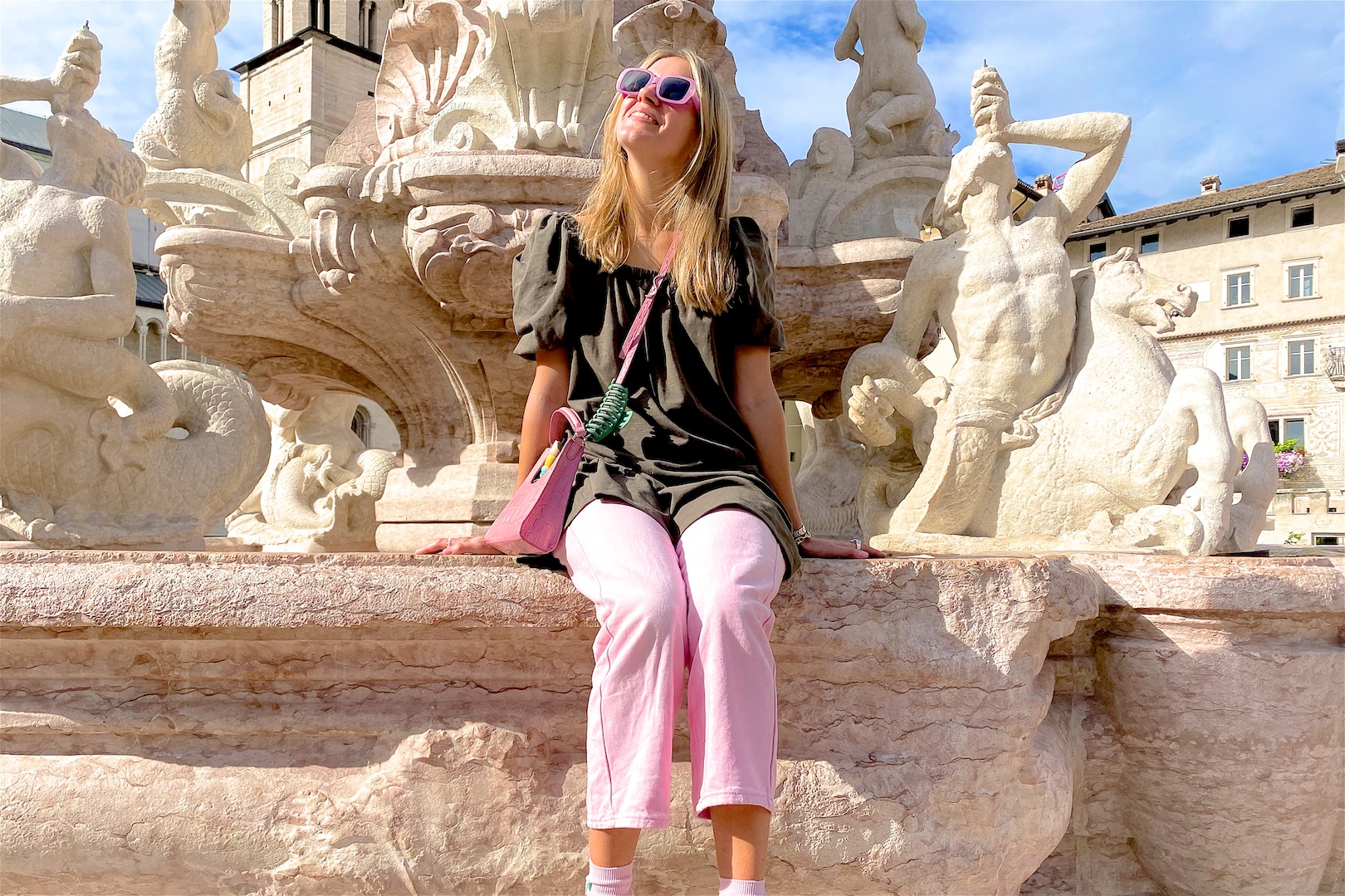 Trento. Fashion Blogger Girl by Style Blog Heartfelt Hunt. Girl with blond hair wearing a green dress, pink denim, pink Staud bag, pink sunglasses, pink socks and chunky sneakers.