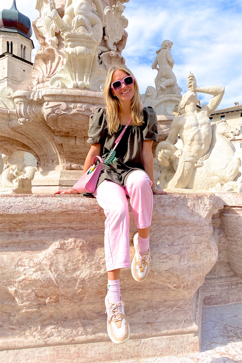 Trento. Fashion and Style Blog Girl from Heartfelt Hunt. Girl with blonde hair wearing a green dress, pink denim, pink Staud bag, pink sunglasses, pink socks and chunky sneakers.