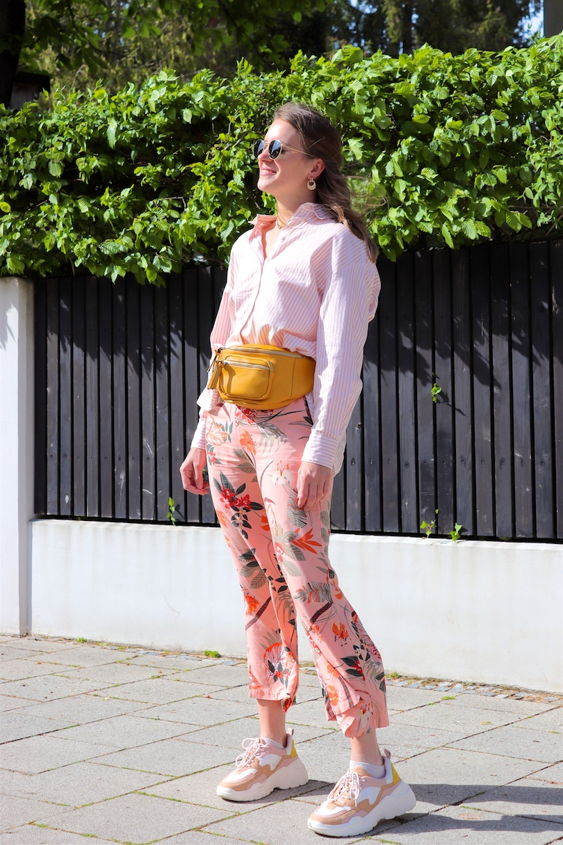 Tropical Flowers. Fashion Blogger Girl by Style Blog Heartfelt Hunt. Girl with blond hair and a pink hair clip wearing pants with tropical flowers, striped shirt, Ray-Ban sunglasses, earrings, yellow belt bag and chunky sneakers.