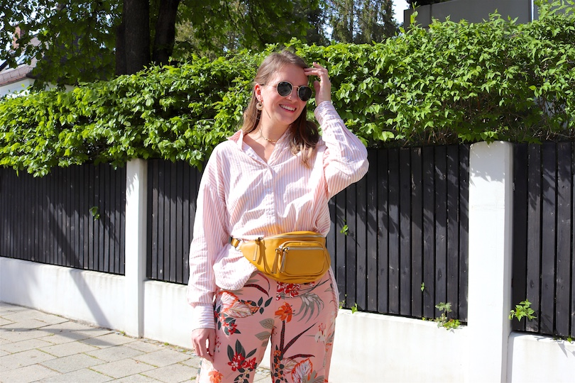 Tropical Flowers. Fashion and Style Blog Girl from Heartfelt Hunt. Girl with blonde hair and a pink hair clip wearing pants with tropical flowers, striped shirt, Ray-Ban sunglasses, earrings, yellow belt bag and chunky sneakers.