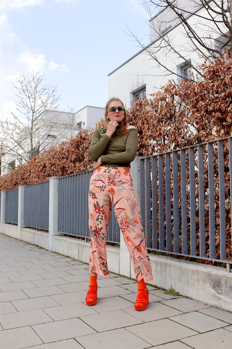 Tropical Pants. Fashion and Style Blog Girl from Heartfelt Hunt. Girl with blonde half-up and half-down hairstyle with green scrunchie wearing tropical pants, cut out top, green sunglasses, green ruched bag, orange socks and orange heels.