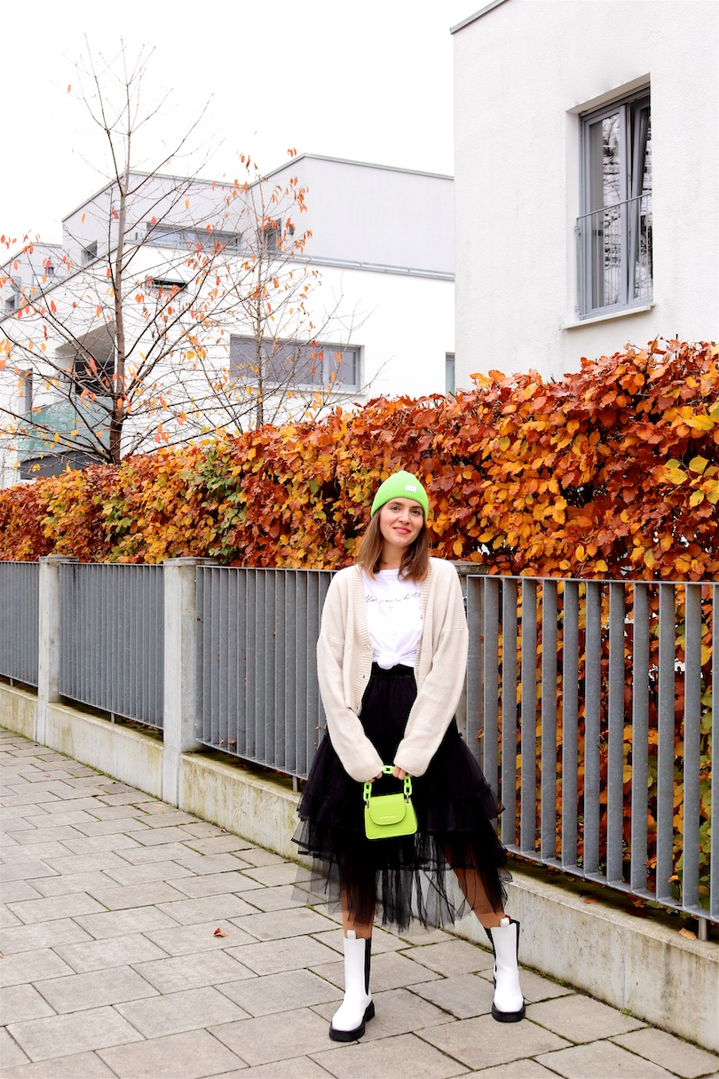 Tulle Day Look. Fashion Blogger Girl by Style Blog Heartfelt Hunt. Girl with blond hair wearing a tulle skirt, white tee, chunky cardigan, green beanie, green bag and white boots.