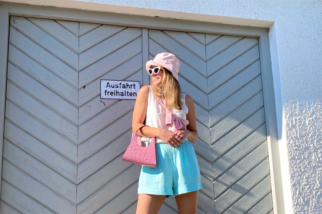 Turquoise Shorts. Fashion Blogger Girl by Style Blog Heartfelt Hunt. Girl with blond hair wearing a turquoise shorts, satin top, floral bucket hat, pink Staud bag and chunky sandals.