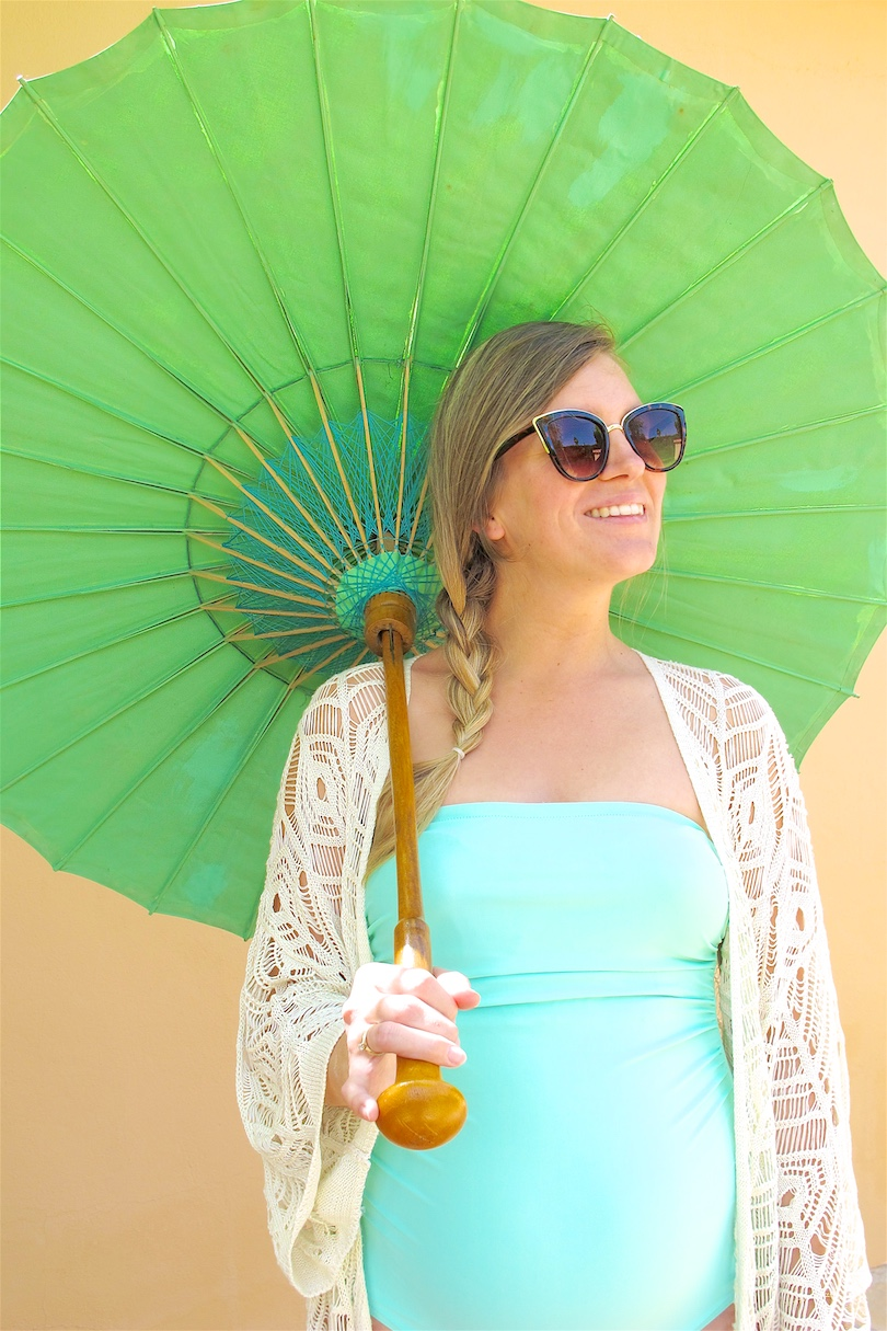 Turquoise Umbrella. Fashion and Style Blog Girl from Heartfelt Hunt. Girl with blonde side braid wearing a turquoise swimsuit and crochet coverup.