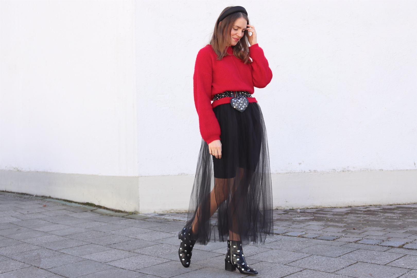 Valentines Tulle. Fashion Blogger Girl by Style Blog Heartfelt Hunt. Girl with blond hair and padded headband a red sweater, tulle skirt, padded headband, studded belt, studded heart bag and studded boots.