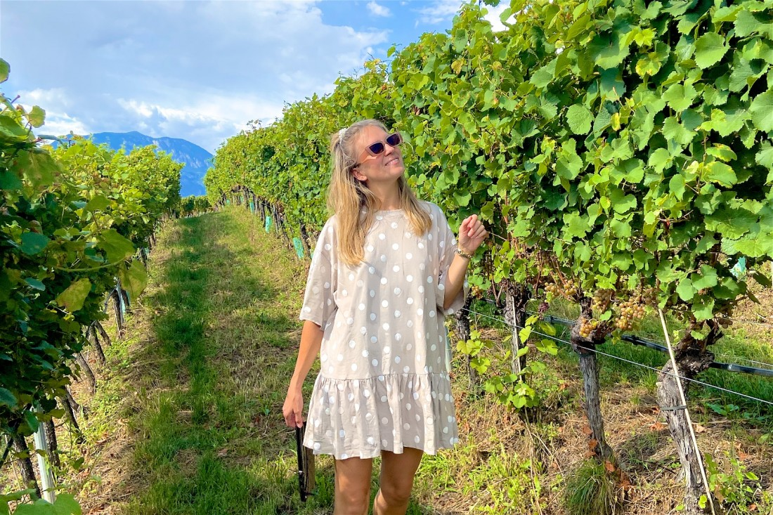 Vineyard Visit. Fashion Blogger Girl by Style Blog Heartfelt Hunt. Girl with blond half-up half-down hairstyle with pearl scrunchie wearing a polka dot dress, slim sunglasses, vintage Gucci bag and quilted sandals.