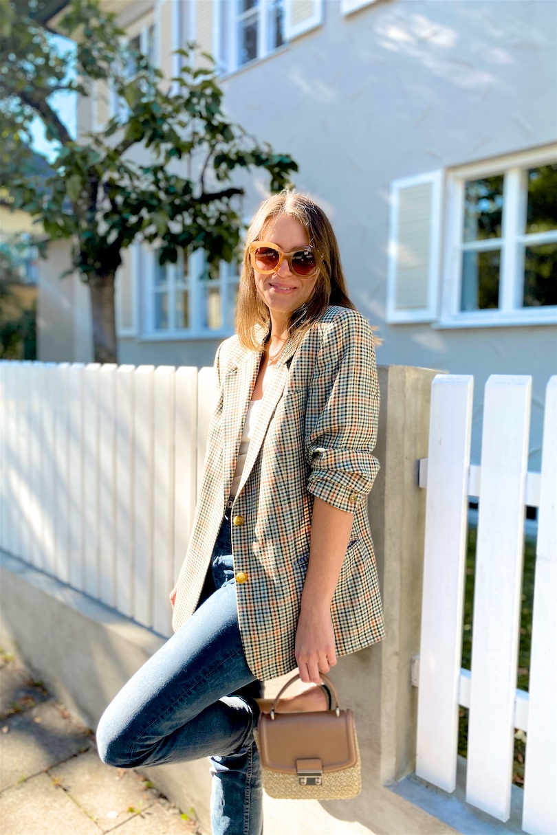 Vintage Blazer. Fashion and Style Blog Girl from Heartfelt Hunt. Girl with blonde hair wearing a checked vintage blazer, oversized sunglasses, mom jeans, straw bag and snake print mules.