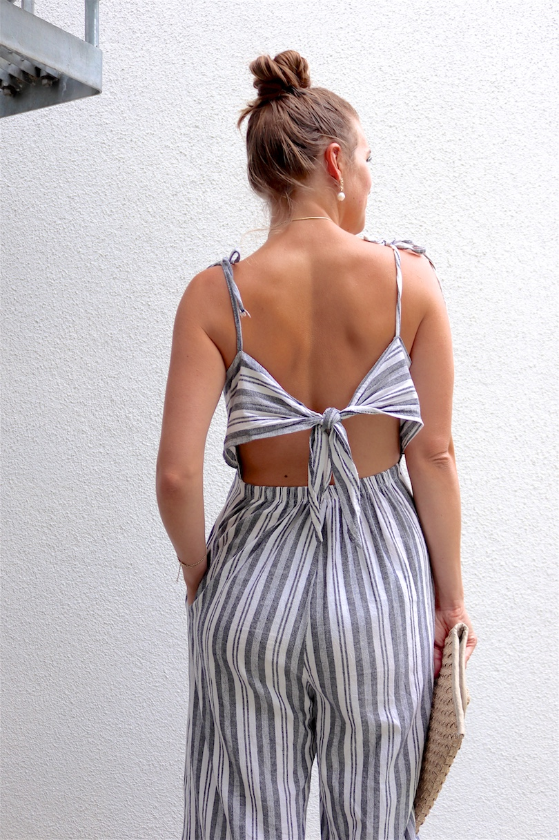 Ways To Wear Jumpsuits. Fashion and Style Blog Girl from Heartfelt Hunt. Girl with blonde high bun and a pearl hair clip wearing a striped jumpsuit, ruffled T-shirt, straw clutch and heels.