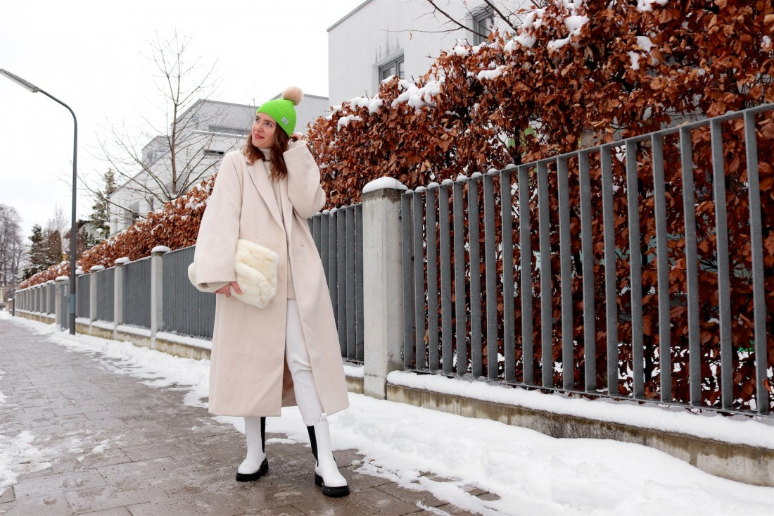 White Coat. Fashion Blogger Girl by Style Blog Heartfelt Hunt. Girl with blond, loose curls wearing a white coat, turtleneck sweater, knitted leggings, green beanie, faux fur pouch bag and white boots.