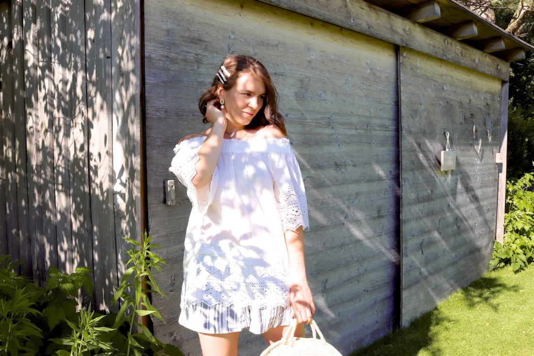 White Off Shoulder Top. Fashion Blogger Girl by Style Blog Heartfelt Hunt. Girl with blond beach waves and pearl hair clips wearing a white off shoulder top, striped shorts, round straw bag and white sandals.