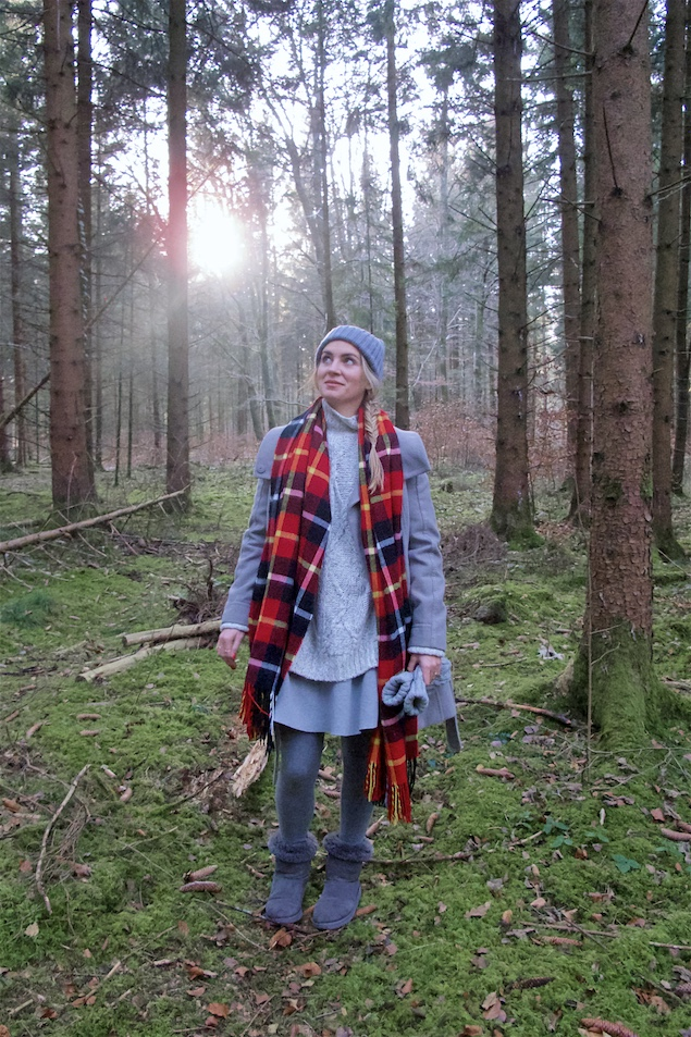 Winter Woods. Fashion Blogger Girl by Style Blog Heartfelt Hunt. Girl with blond fishtail braid wearing a heavy knit sweater, flared skirt, coat, pompom beanie, plaid scarf, mittens and Ugg boots.