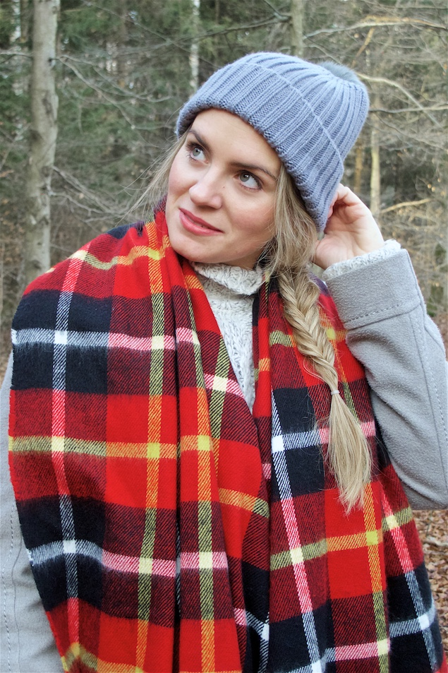 Winter Woods. Fashion and Style Blog Girl from Heartfelt Hunt. Girl with blonde fishtail braid wearing a heavy knit sweater, flared skirt, coat, pompom beanie, plaid scarf and Ugg boots.