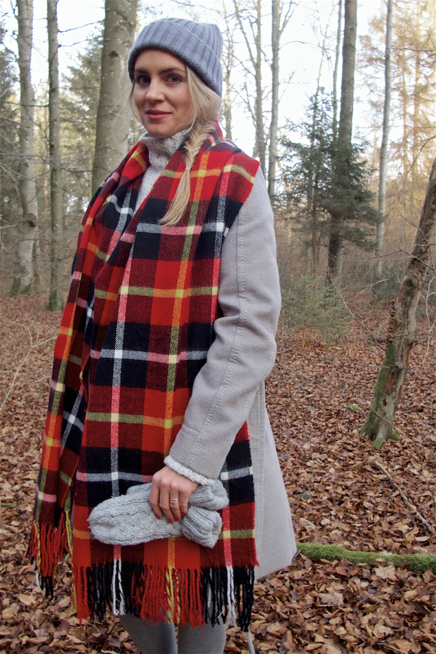Winter Woods. Fashion and Style Blog Girl from Heartfelt Hunt. Girl with blonde fishtail braid wearing a heavy knit sweater, flared skirt, coat, pompom beanie, plaid scarf, mittens and Ugg boots.