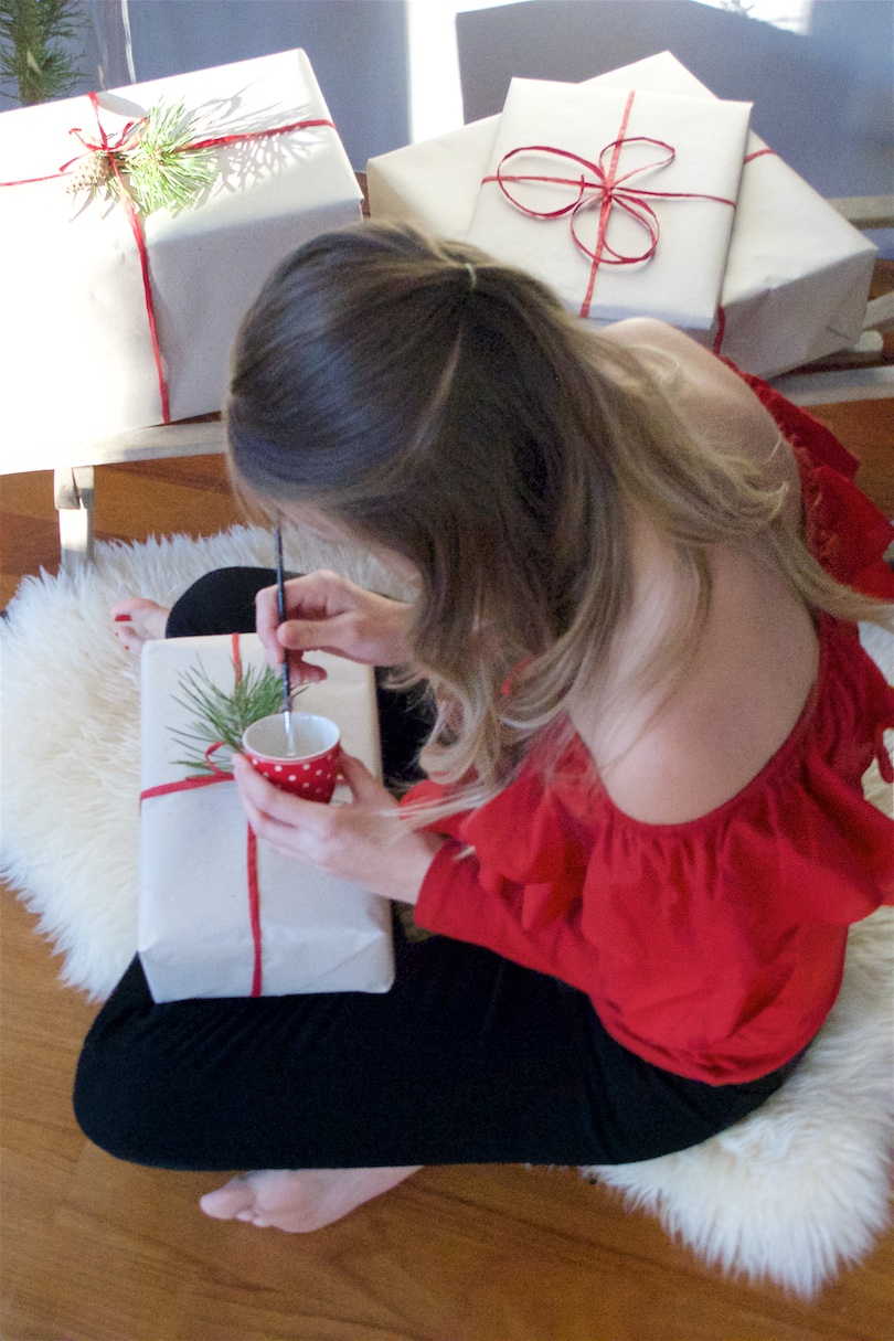 Wrapping Christmas Presents. Fashion and Style Blog Girl from Heartfelt Hunt. Girl with a sled and blonde half-up half-down hairstyle with loose curls wearing a red off shoulder top and black jeans.