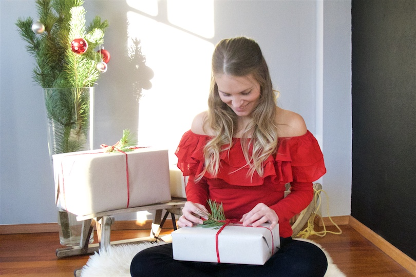 Wrapping Christmas Presents. Fashion Blogger Girl by Style Blog Heartfelt Hunt. Girl with a sled and blond half-up half-down hairstyle with loose curls wearing a red off shoulder top and black jeans.