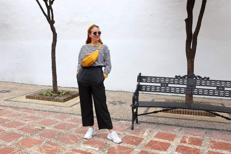 Yellow Belt Bag. Fashion Blogger Girl by Style Blog Heartfelt Hunt. Girl with blond hair and yellow headband wearing a yellow belt bag, striped top, faux leather culotte, Ray-Ban sunglasses and chunky sneakers.